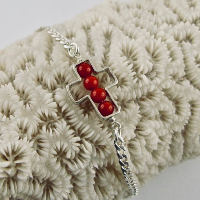 Une chaîne maille gourmette et 4 perles 4 mm de véritable corail rouge de Méditerranée, délicatement enchâssées dans une croix ajourée, en argent 925/1000e