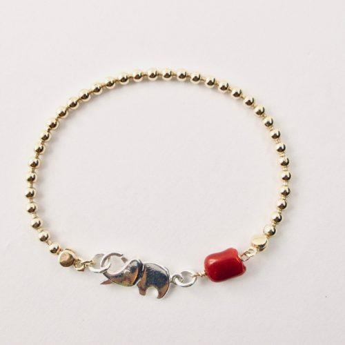 Le bracelet Kokkiri, avec son fermoir en forme d'éléphant en argent 925/1000e, est composé d'une chaîne boule en argent plaqué or et d'une grosse perle irrégulière de véritable corail rouge de Méditerranée
