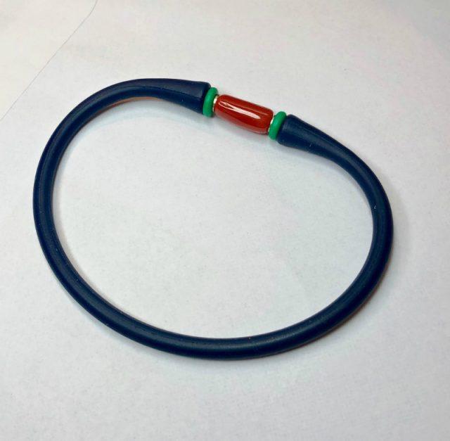 Bracelet pour l'homme, en caoutchouc, avec sa barette de véritable corail rouge de Méditerranée monté sur tige acier.