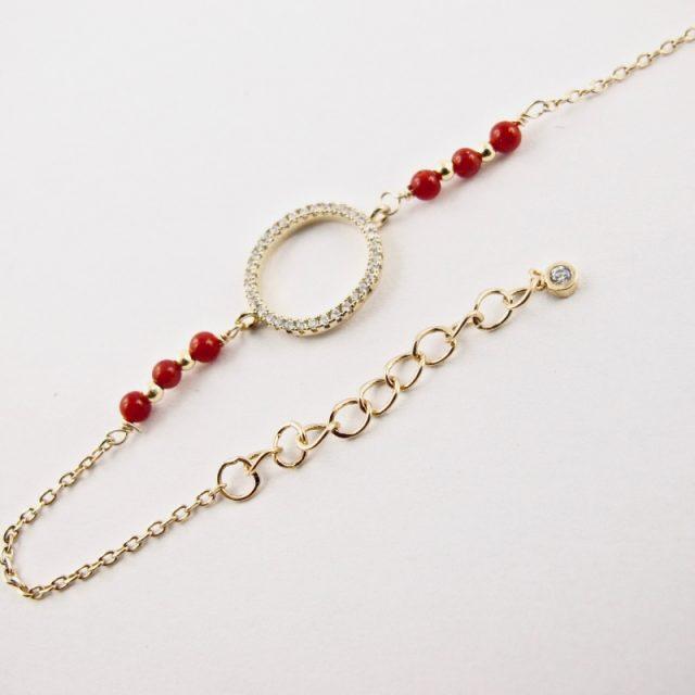 Ce bracelet estcomposé d'une fine chaîne en argent plaqué or et perles 2,5mm de véritable corail rouge de Méditerranée, reliée à un anneau (ø 13mm) serti de cristaux de swarovski.