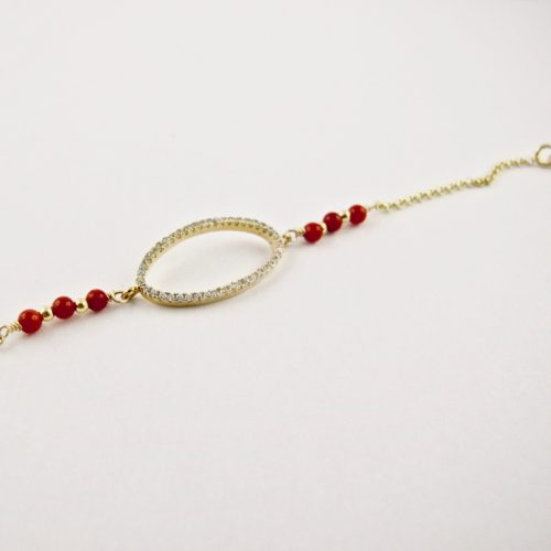 Ce bracelet estcomposé d'une fine chaîne en argent plaqué or et perles 2,5mm de véritable corail rouge de Méditerranée, reliée à un anneau ovale serti de cristaux de swarovski.