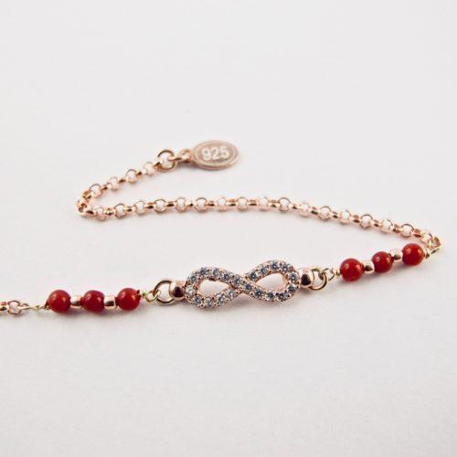 Ce bracelet estcomposé d'une fine chaîne en argent plaqué or rose et perles 2,5mm de véritable corail rouge de Méditerranée, reliée à un infini serti de cristaux de swarovski.