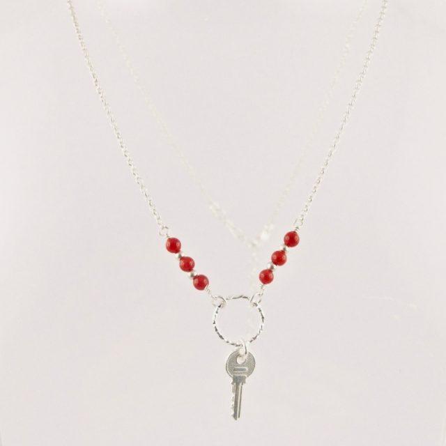 Ce collier estcomposé d'une fine chaîne en argent massif et perles 2,5mm de véritable corail rouge de Méditerranée. Un anneau en argent martelé porte le petit charms.