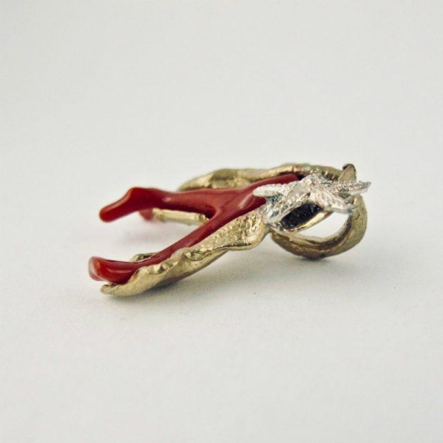 Pendentif ramo, branche de véritable corail rouge de Méditerranée enveloppée d'une feuille de bronze plaqué or, ornée d'une petite étoile de mer en argent massif.