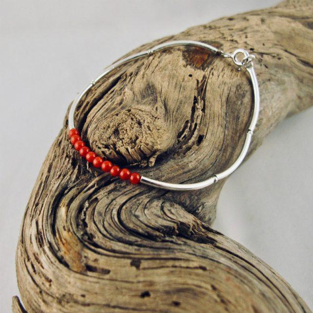 Bracelet composé d'une constellation de 10 perles de 3 mm de véritable corail rouge de Méditerranée,et de tubes jonc de 2 cm en argent 925